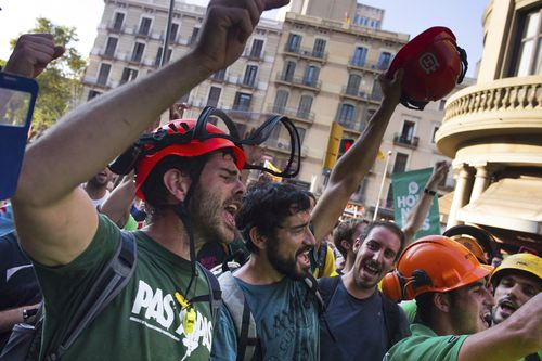 People shout slogans as they demonstrate at University square, in downtown Barcelona. (AAP)