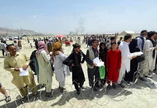 In this August 17  file photo hundreds of people gather outside the international airport in Kabul, Afghanistan.
