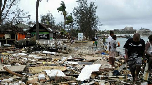 Locals sift through rubble from Cyclone Pam in Port Vila, Vanuatu. (AAP)