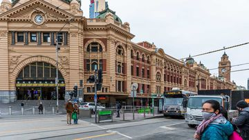 Pedestrians wearing masks outside Flinders Street station in Melbourne.