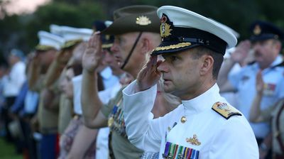 Commodore Brenton Smyth and Commander 1st Brigade, Brigadier John Frewen salute during the 2014 Anzac Day Dawn Service in Darwin. (AAP)