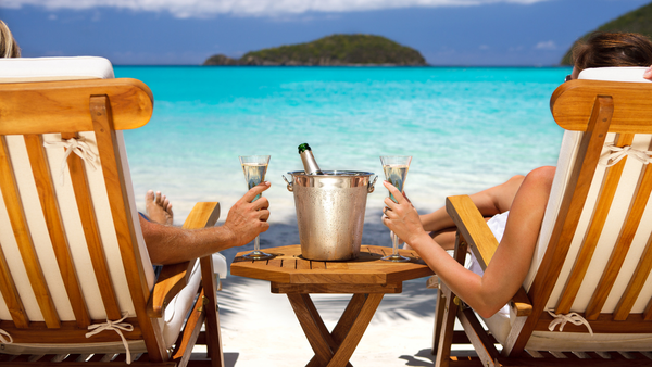 Couple drinking champagne in sun chairs on a beach | Honeymoon holiday couple