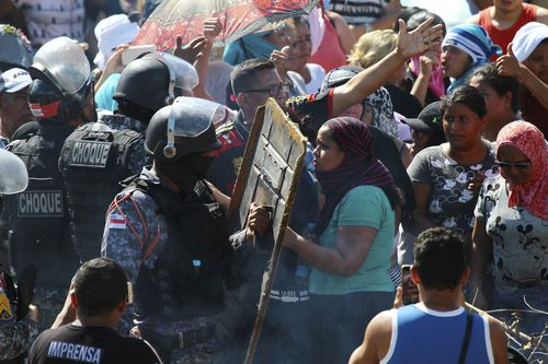 Protestors argue with police outside the Anisio Jobim Prison Complex where a riot erupted among inmates in the northern state of Amazonas, Brazil, Sunday.