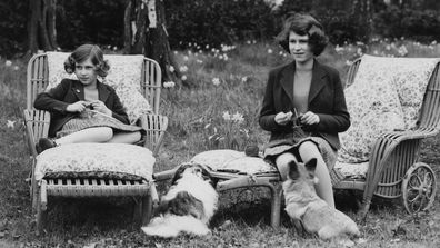 Princess Elizabeth (now Queen Elizabeth II, right) and her younger sister Princess Margaret Rose (1930 - 2002) knitting for the forces in the grounds of the Royal Lodge in Windsor Great Park, April 1940