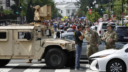 A checkpoint blocks traffic on 16th Street Northwest as people gather near the White House, Saturday, June 6, 2020