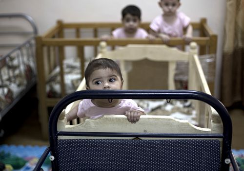 Baby girls stand up in their cribs at Salhiya Orphanage, which now hosts foreign and Iraqi children of Islamic State militants, in Baghdad, Iraq. The war to drive out Islamic State militants left tens of thousands of orphans, a generation that Iraq is struggling to care for.