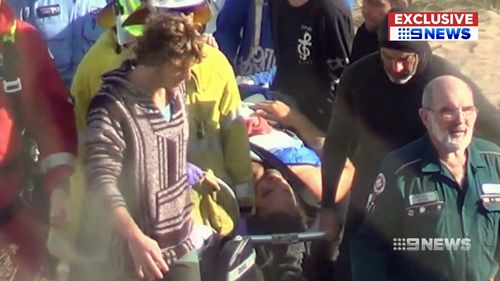 Mr Travaglini's friends carried him up the beach on a surfboard. (9NEWS)