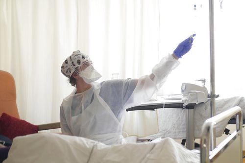 In this March 19, 2021, file photo, a nurse tends to a patient affected by COVID-19 virus in the ICU unit at the Ambroise Pare clinic in Neuilly-sur-Seine.
