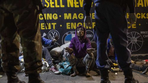 A homeless woman is confronted by soldiers in Johannesburg, South Africa.