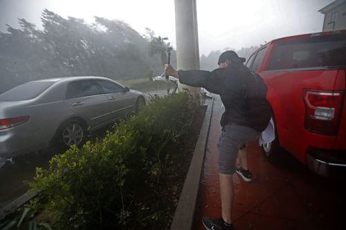 A storm chaser films from underneath a hotel canopy during Hurricane Michael in Panama City Beach