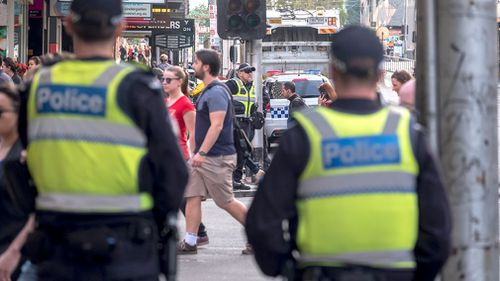 Victorian police officers stand guard in the aftermath of Thursday's Flinders Street rampage.