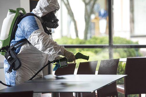 Service technician Hazel Maldonado of Guardian Touchless Solutions wears a protective suit as he uses an electrostatic gun to clean Villaggio del Vino in Tyler, Texas.