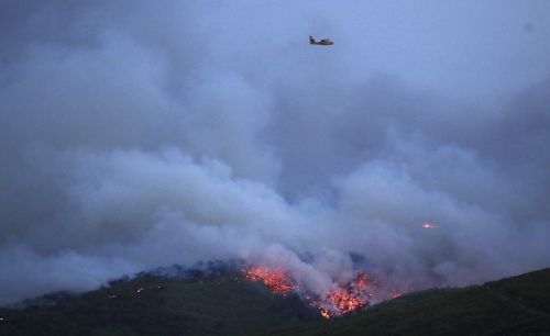 A plane flies over the smoke billowing from a wildfire in the Athens town of Mati. Picture: AAP
