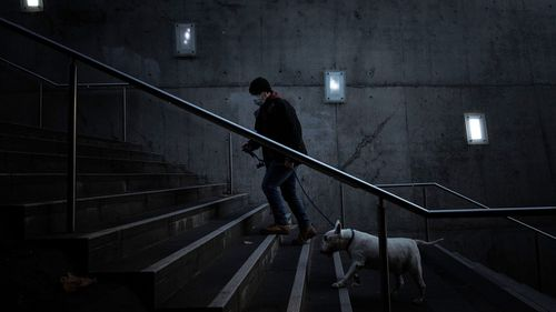 A man wearing a mask walks his dog at Southbank.