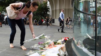 Bunches of flowers rest beside bollards, which have been sanctioned off with police tape, near the Lindt Café. (AAP)