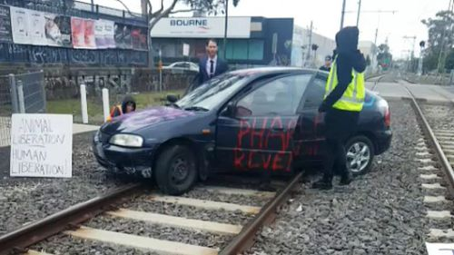 Protestors drove a car onto train tracks near Flemington. (AAP)