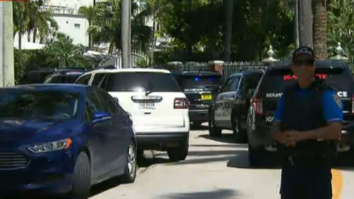 A Miami police officer stands on the street outside the mansion. (Local 10 News)