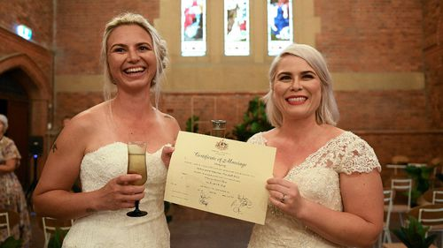 Sarah Turnbull (left) and Rebecca Hickson pose for a photograph with their Certificate of Marriage. (AAP)