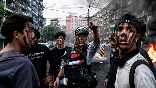 """As the United Nations Security Council discussed Myanmar's military coup on Wednesday, the country's junta declared a """"ceasefire"""". Protesters are shown with their faces painted standing near a burning makeshift barricade during a protest against the military coup, in Yangon on Tuesday."""