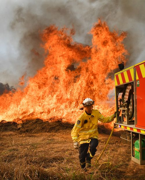 New South Wales Rural Fire Service firefighters are seen back burning and fighting fires on Long Gully Road in the northern New South Wales town of Drake, Monday, September 9, 2019.