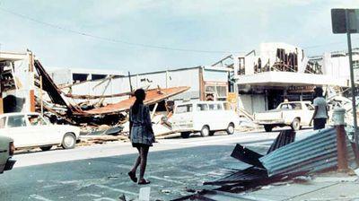 A woman strolls through the devastation.