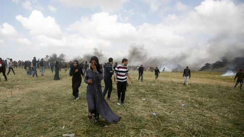 Palestinian protesters run to cover from teargas fired by Israeli soldiers during clashes with Israeli troops along the Gaza Strip border with Israel, east of Khan Younis. (AP)