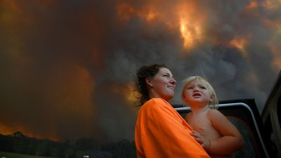 Sharnie Moren and her 18-month-old daughter Charlotte look on as thick smoke rises from bushfires near Nana Glen, near Coffs Harbour.
