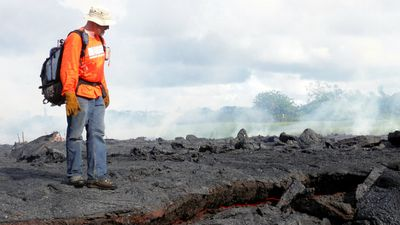 A Hawaii Volcano Observatory geologist stands on top of the partially-cooled lava flow, with the red hot interior still visible beneath. (AAP)