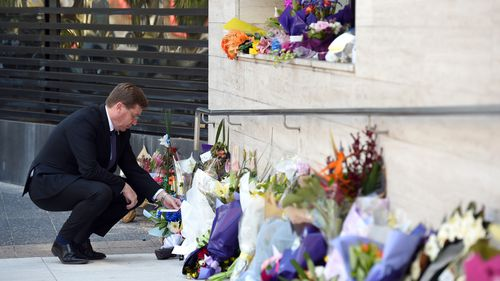 NSW Police Minister Troy Grant looks at flowers placed for police employee Curtis Cheng outside of the NSW Police Headquarters in Sydney on Tuesday, Oct. 6, 2015. Mr Cheng died at the scene after being shot by 15-year-old gunman Farhad Jabar Khalil Mohammad, was killed by officers responding to the shooting.
