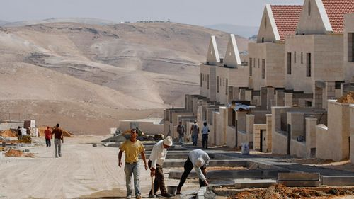 In this file photo of Tuesday, June 9, 2009, Palestinian men work at a construction site in the West Bank Jewish settlement of Maaleh Adumim, near Jerusalem.  (AAP)