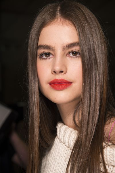 A perfect red-orange lip worn with bare skin and lashes, lashes, lashes.