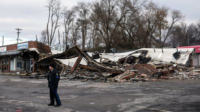 A policeman stands near one of the burnt businesses in West Florissant Avenue, Ferguson, which is now closed pending an investigation. 61 people were arrested during violent protests overnight. (AAP)
