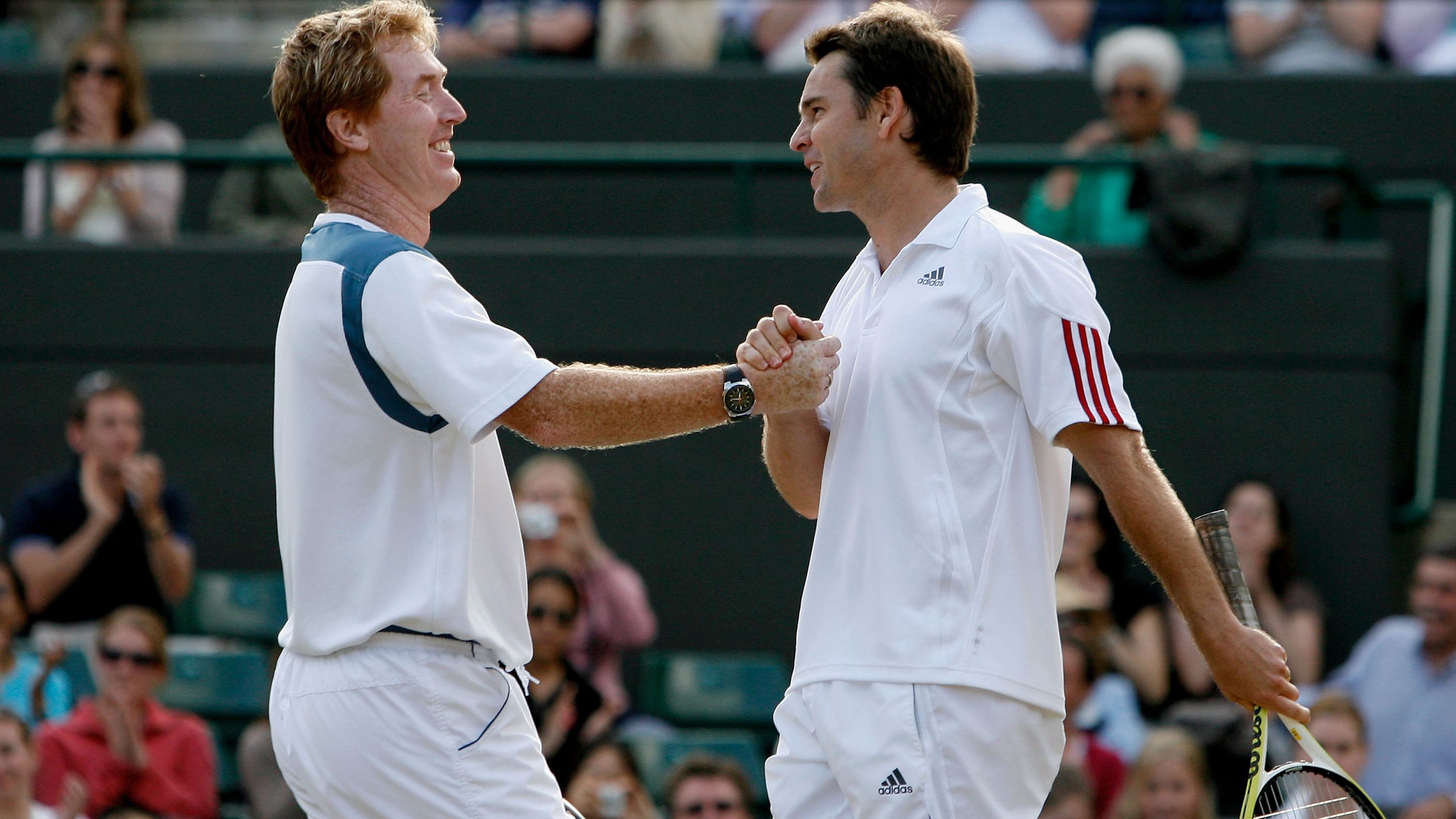 Mark Woodforde and Todd Woddbridge come together after a Wimbledon victory.