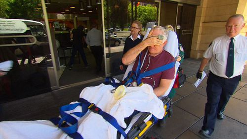 Andrew Thomas Philips hid his face as a paramedic wheeled him out of court today.