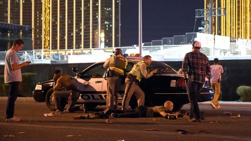 Police crouch behind a patrol car with their weapons trained on the casino. (Getty Images)