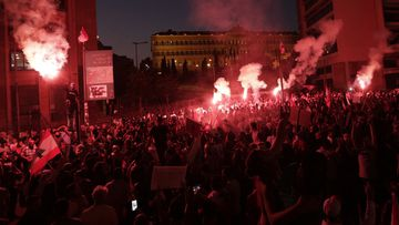 Anti-government protesters light flares and shout slogans against the Lebanese government during a protest in Beirut, Lebanon, Monday, Oct. 21, 2019.