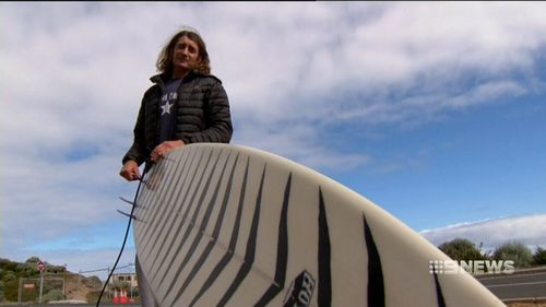 Robby Bruce, 60, has described the moment a shark swiped him clean off his surf board. (9NEWS)