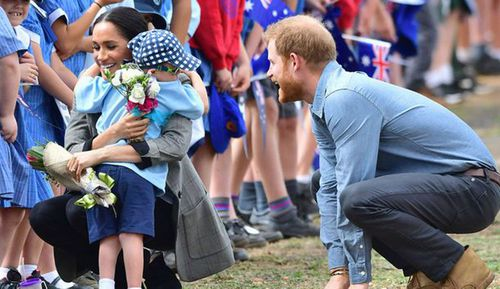 As the Royals worked their way along a line of schoolchildren from Dubbo, five-year-old Luke Vincent presented Meghan with flowers before embracing Harry.