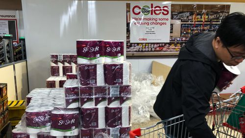 A customer fills his cart with packs of toilet paper at a shopping centre in Sydney.