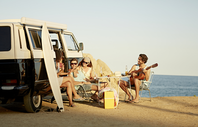 Van life: people gathered around a camper at the beach