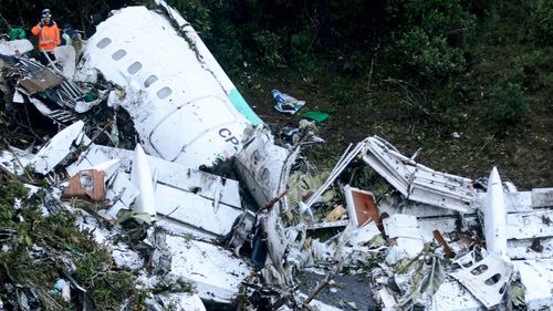 Crews inspect the wreckage of the crashed charter plane in Colombia. (AAP)