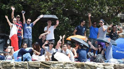 New Year's Eve revellers wave from the foreshore having claimed a good spot. (AAP)