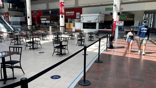 People walk past the nearly empty food court in Rhode Island. A new unit of the Rhode Island State Police will be enforcing the state's limitations on social gatherings.