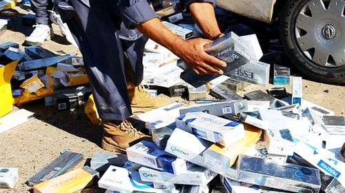 Militants prepare to burn a pile of confiscated cigarettes.