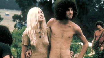 A hippie couple pose together arm in arm with others around them, during the Woodstock music festival in 1969.