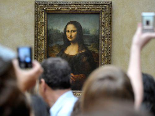 Visitors take pictures of Leonardo da Vinci's Mona Lisa, at the Louvre Museum in Paris