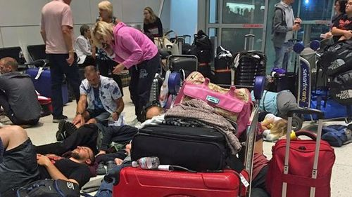 Passengers try to rest on the floor at a terminal in JFK Airport. (Twitter)