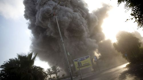 Smoke raises in the background following an Israeli airstrike hits a governmental building in Gaza City, 14 July, 2018. (AAP)