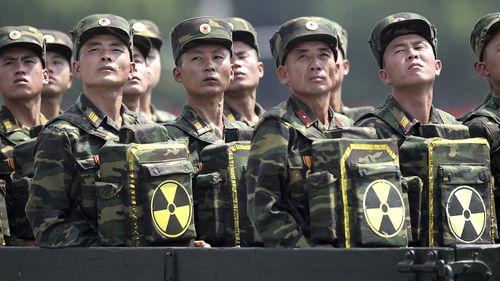 North Korean troops carrying bags bearing a nuclear logo at a parade. (AAP)