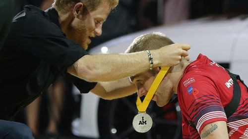 Harry awards the silver medal to Omrod. (Getty)